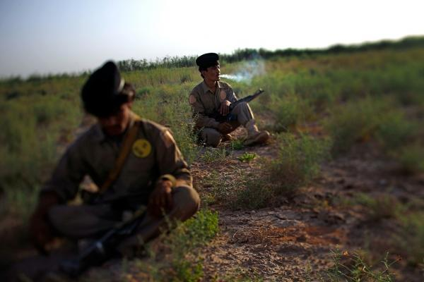 Isutalah (left) and Mohammed Gul are part of a local defense force known as Interim Security for Critical Infrastructure, or ISCI, in Helmand province, Afghanistan. Here, they take a break from patrolling with Marines from Golf Company, 2nd Battalion, 8th Regiment during a joint operation with Afghan army soldiers in northern Marjah.
