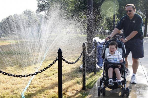Ron Krajewski of San Diego, Calif., pushes his son through a water sprinkler to beat the simmering heat in Washington, D.C.