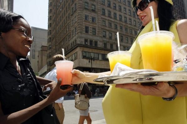 Stephanie Guerilus buys a cold lemonade in the hot Philadelphia sun from Lisa Tobin, who surely is sweltering in her lemon costume.