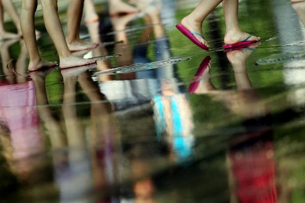 Children's feet are reflected in a fountain at Battery Park in New York City. Some schools in the Northeast planned to close early Thursday so students would not have to suffer in buildings without air conditioning.