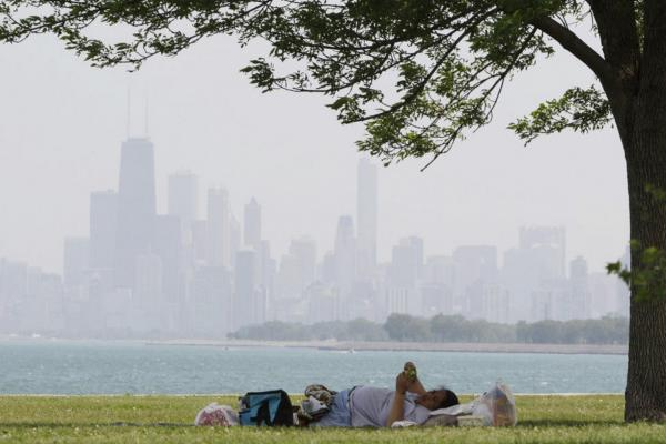 A woman rests in the shade at Montrose beach in Chicago. Cooling centers have opened in Chicago, Memphis, Tenn., and Newark, N.J., as a refuge for those without air conditioning.
