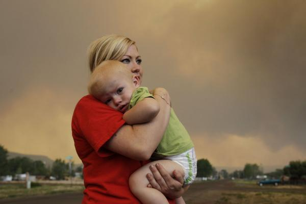 Emily Shupe comforts her 18-month-old son Jax as the family prepares to evacuate to Phoenix as the Wallow Fire approaches in Springerville, Ariz. It officially became the second-largest wildfire in Arizona history on Tuesday.