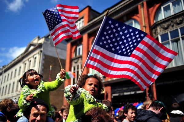 Children wave U.S. flags as they wait to see Obama address a rally at College Green in Dublin.