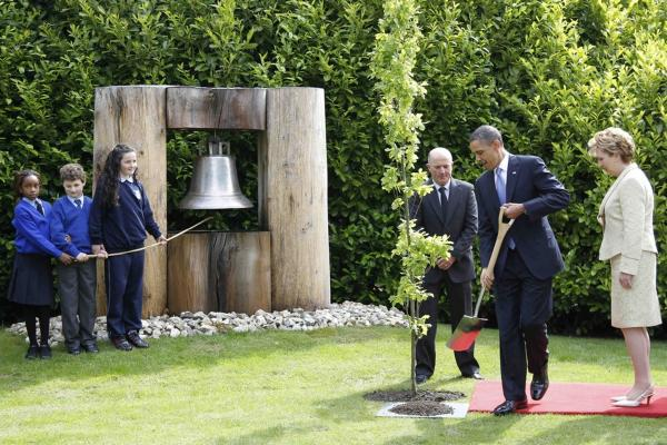Obama plants a tree at the Peace Bell with Ireland's President Mary McAleese.