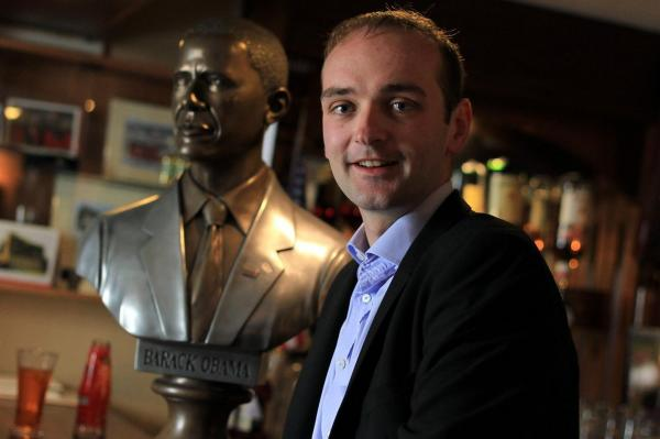 An eighth-cousin of Obama, Henry Healy, poses with a bust of the president in Ollie Hayes Pub.