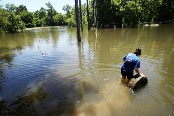 MAY 16: Barbara Fontanille recovers a tire from the rising waters of the Atchafalaya River in Simmesport, La. Her family has no flood insurance and have relocated to a trailer provided by FEMA.