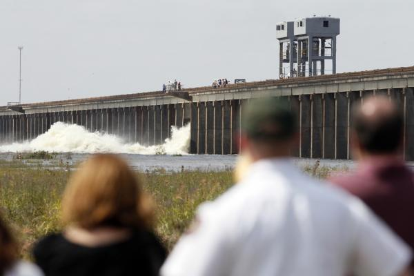 MAY 14: People watch as water diverted from the Mississippi River spills through a bay in Morganza, La. A  floodgate was slowly raised for the first time in nearly four decades, unleashing a torrent of water from the Mississippi River.