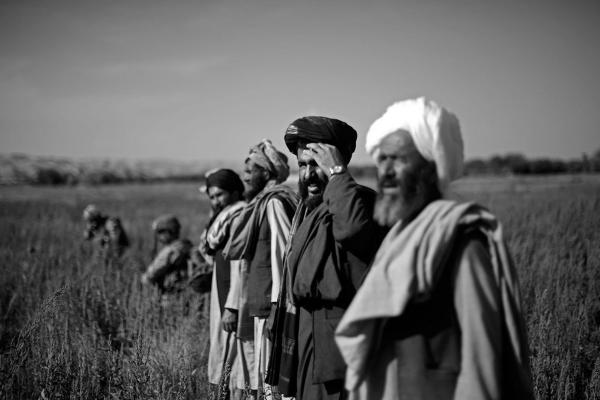 "A group of Afghan farmers stand in the middle of a Marine patrol passing through the ""green zone."""