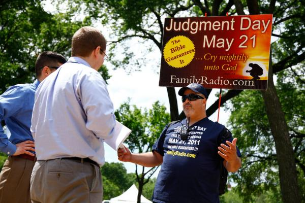 David Liquori (right) talks to two men on National Mall in Washington, D.C., on Friday. The Long Islander has been speaking about Judgment Day for 23 years. His passion for the message resulted in the end of his marriage because his wife had different views. His 12-year-old son is skeptical of his father's views, and Liquori worries about him. He isn't sure how he plans to spend May 21, but he thinks it will be a solemn day.