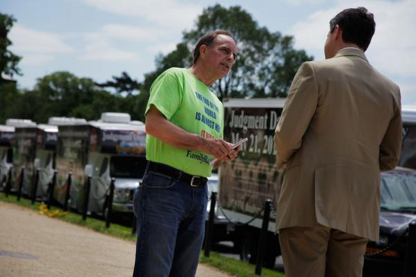 Fred Store engages a passerby in conversation as he passes out tracts on the Mall. The retired electrician has been listening to Family Radio since 1983, and in September he joined the caravan project, which travels throughout the country to warn people of Judgment Day. There are five trucks per caravan and five active caravans.