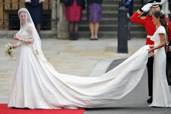 Kate Middleton walks toward Westminster Abby with the help of her sister. Her dress was designed by Sarah Burton for Alexander McQueen.