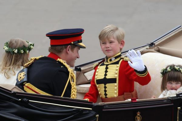 Prince Harry (left), page boy Tom Pettifer and bridesmaid Eliza Lopes (right) travel by carriage to Buckingham Palace.