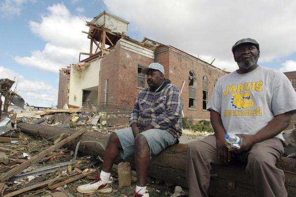 Sal Merritt and Edrich Barnes rest outside the remains of Alberta Baptist Church in Tuscaloosa.