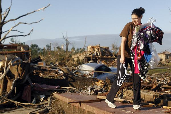 Tiffany Wood carries clothes from her home, a day after a tornado hit Pleasant Grove, Ala.