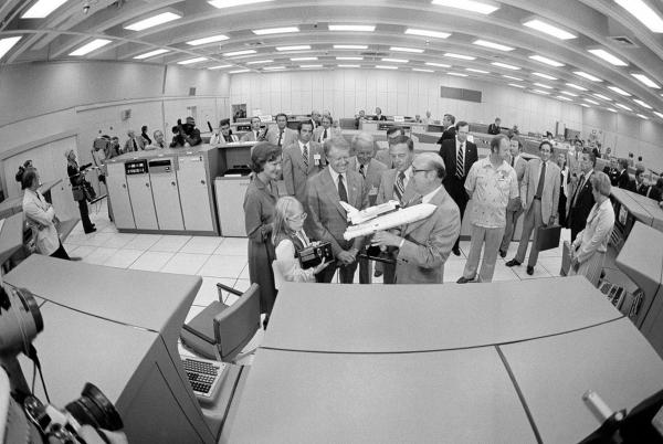 NASA Administrator Robert Froscoch (right) shows a model of the space shuttle to President Jimmy Carter, first lady Rosalynn Carter and daughter Amy during their visit to the firing room of the Launch Control Center at Cape Canaveral in October 1978.