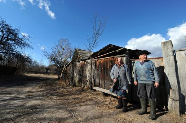 Ivan Semenyuk, 75, and his wife, Maria, 73, stand outside their house in the largely abandoned village of Paryshiv, inside the exclusion zone, in March 2011.