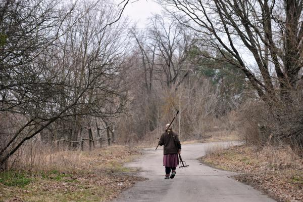 Ganna Zavorotnya, 78, carries her tools as she walks to her vegetable garden in Kupovate, inside the exclusion zone, in April 2011.