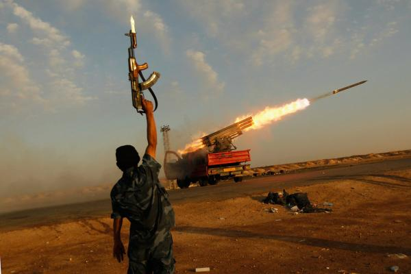 A rebel fighter celebrates as his comrades fire a rocket barrage toward the positions of troops loyal to Libyan ruler Moammar Gaddafi, April 14, west of Ajdabiyah.