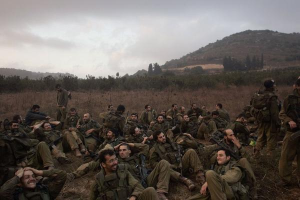 Exhausted Israeli soldiers gather on the Israeli-Lebanese border after marching in from Lebanon the morning of Aug. 14.