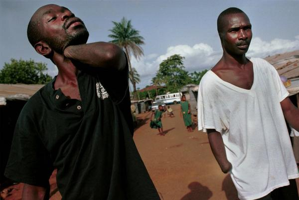 Men missing arms and ears walk around a camp for amputees in Freetown, Sierra Leone, June 5, 2001.