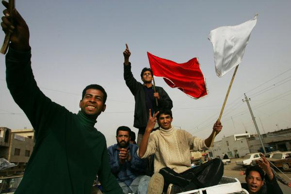 Men brandish flags during a parade celebrating the Shiite festival of Al Ghadeer in the Sadr City neighborhood of Baghdad, Jan. 29, 2005.