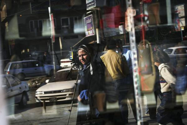 A woman is reflected in a Baghdad shop window on a busy boulevard, Feb. 3, 2005.