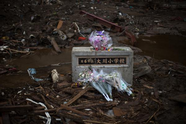 A month after the earthquake and tsunami devastation, flowers are offered Monday Okawa Elementary school in Ishinomaki, Miyagi prefecture on Monday. Japan fell silent at 2:46 pm to mark exactly one month since the disaster.