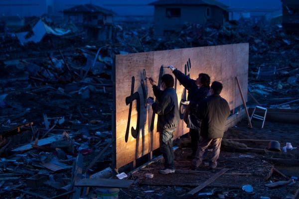 "Tsunami survivor Kenichi Kurosawa (center) and his friends draw words that translate to ""hang in there"" on a billboard in Ishinomaki, Miyagi prefecture."