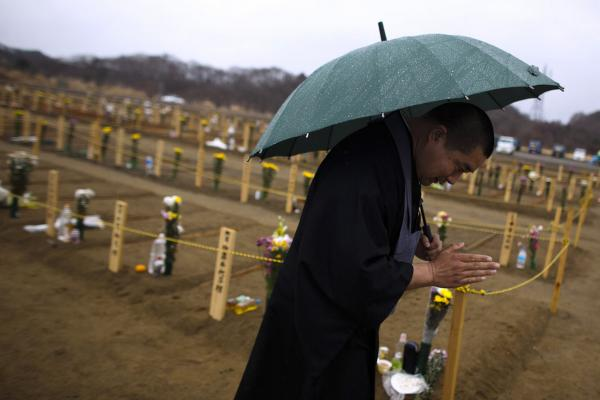 A Buddhist monk prays for earthquake victims at a burial site in Higashimatsushima, Miyagi prefecture. A tsunami warning was issued Monday after a 6.6 aftershock struck south of Fukushima.