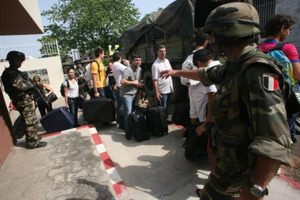 Members of the France's military help French nationals and other foreigners evacuate from a hotel in Abidjan on Thursday. France has evacuated 2,430 foreigners, including French citizens and those of other countries from the fighting in Abidjan.