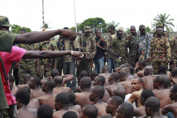 Ouattara's soldiers point to men they claim to recognize among several dozen prisoners captured during fighting and patrols in Abidjan, Ivory Coast on Wednesday.