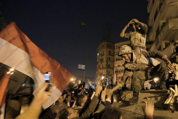 Egyptian soldiers celebrate with anti-government protesters. Vice President Omar Suleiman announced the military will take control over affairs of state.