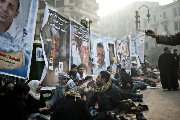 In the early hours Friday, anti-government demonstrators rest in front of posters of people killed during the latest political crisis.