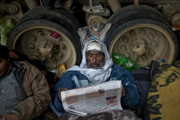A protester reads a newspaper while resting against an army tank in Tahrir Square on Friday.