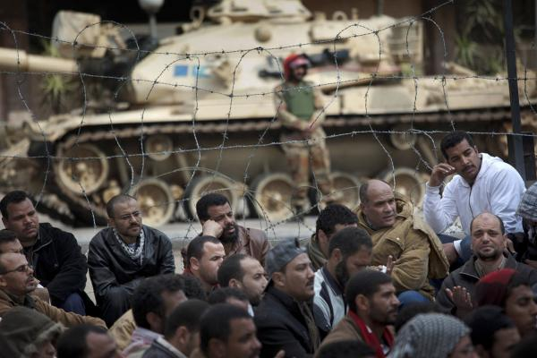 A soldier stands guard next to a tank as crowds protest in front of the state television building in downtown Cairo on Friday.