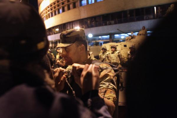 An Egyptian army officer speaks to anti-government protesters outside the national television building after President Mubarak's Thursday address to the nation.