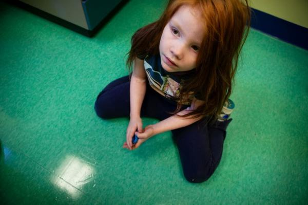 Katie looks up at her mother from the floor of the doctor's office. The symptoms of lead poisoning include behavioral problems, headaches and sleeplessness. But Moore says it's especially hard to detect symptoms in kids with learning disabilities.