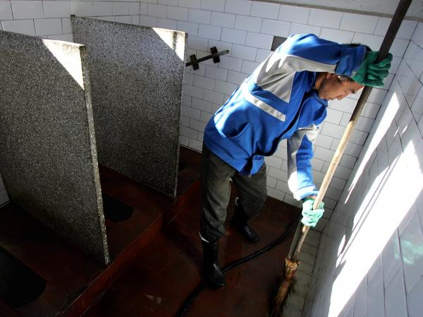 A worker cleans a public bathroom in Beijing. New rules require that public restrooms in the Chinese capital have no more than two flies in them.