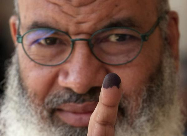 An Egyptian man shows his ink-stained finger after voting in Cairo earlier today.