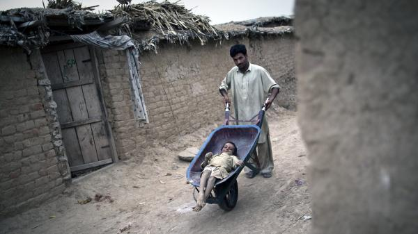 A Pakistani man wheels Jamshid, an 8-year-old girl with polio, around the outskirts of the capital Islamabad last July.
