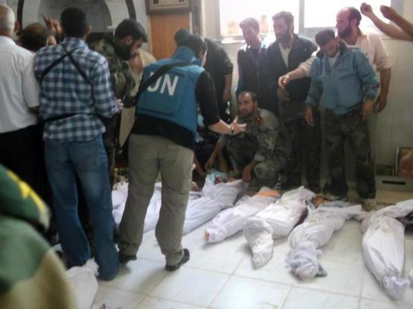 A handout picture released by the Syrian opposition's Shaam News Network shows UN observers at a hospital morgue in the central Syrian town of Houla on Saturday.