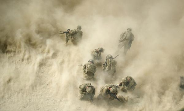 U.S. soldiers gather near a destroyed vehicle and protect their faces from dust blown by a helicopter — known as rotor wash — as their wounded comrades are airlifted by Medevac from the 159th Brigade Task Force Thunder to Kandahar Hospital Role 3. Three soldiers were wounded while their vehicle was destroyed up by an improvised explosive device.