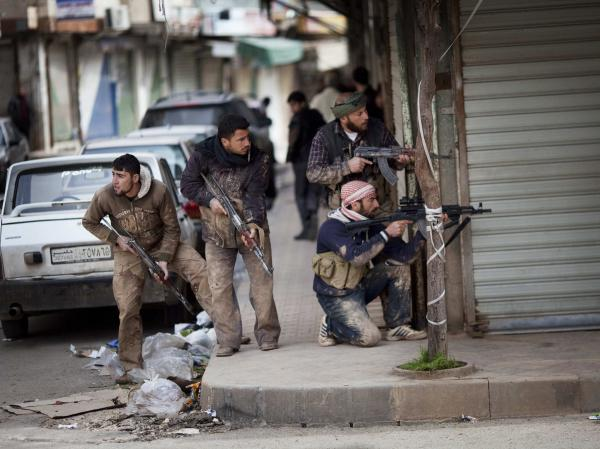 Syrian rebels take position during clashes with government forces in Idlib, north Syria.