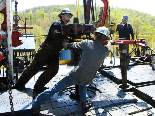 Workers move a section of well casing into place at a natural gas drilling rig near Burlington, Pa. The industry is expected to drill as many as 10,000 new wells in the next few  years.