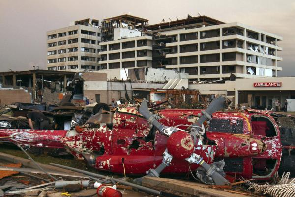 A destroyed helicopter lies on its side in the parking lot of the St. John's Regional Medical Center in Joplin.