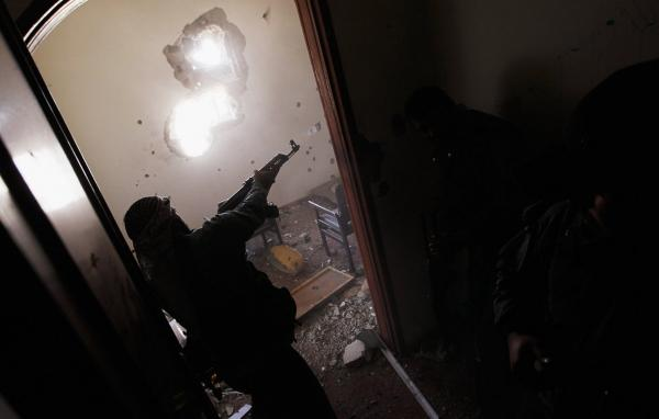 A Libyan rebel fighter fires on trapped government loyalist troops in a house in Misrata.