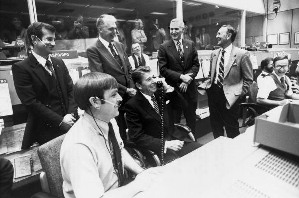 Making an extremely long-distance call, President Ronald Reagan (seated at center) speaks with the crew of the second space shuttle flight from Houston in November 1981.  He jokingly asked if they could stop by Washington en route to their California landing site so he could come along with them.
