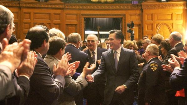 Mitt Romney shakes hands as he walks into the House Chambers during inaugural ceremonies at the State House in Boston in 2003. the Obama campaign sought to focus attention on Romney's tenure as Massachusetts governor.