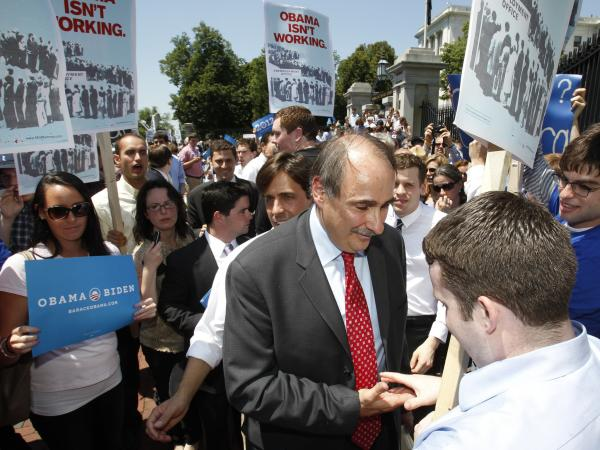 David Axelrod, the Obama campaign's senior strategist (center), stops to shake a demonstrator's hand as he leaves a news conference at the Massachusetts State House in Boston on Thursday.