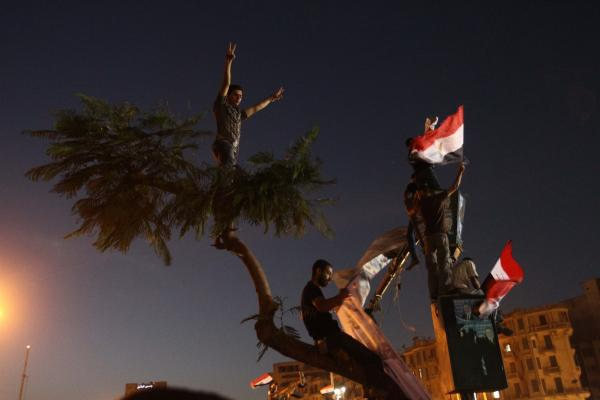 Protesters hold Egyptian flags during the demonstration in Tahrir Square.